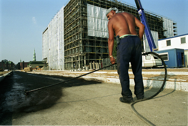 Worker spraying tar in front of SAP building at the new Harbour City
