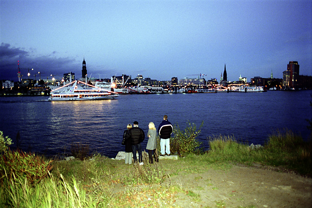Tourists watching Hamburgs skyline from the other side of the Elbe